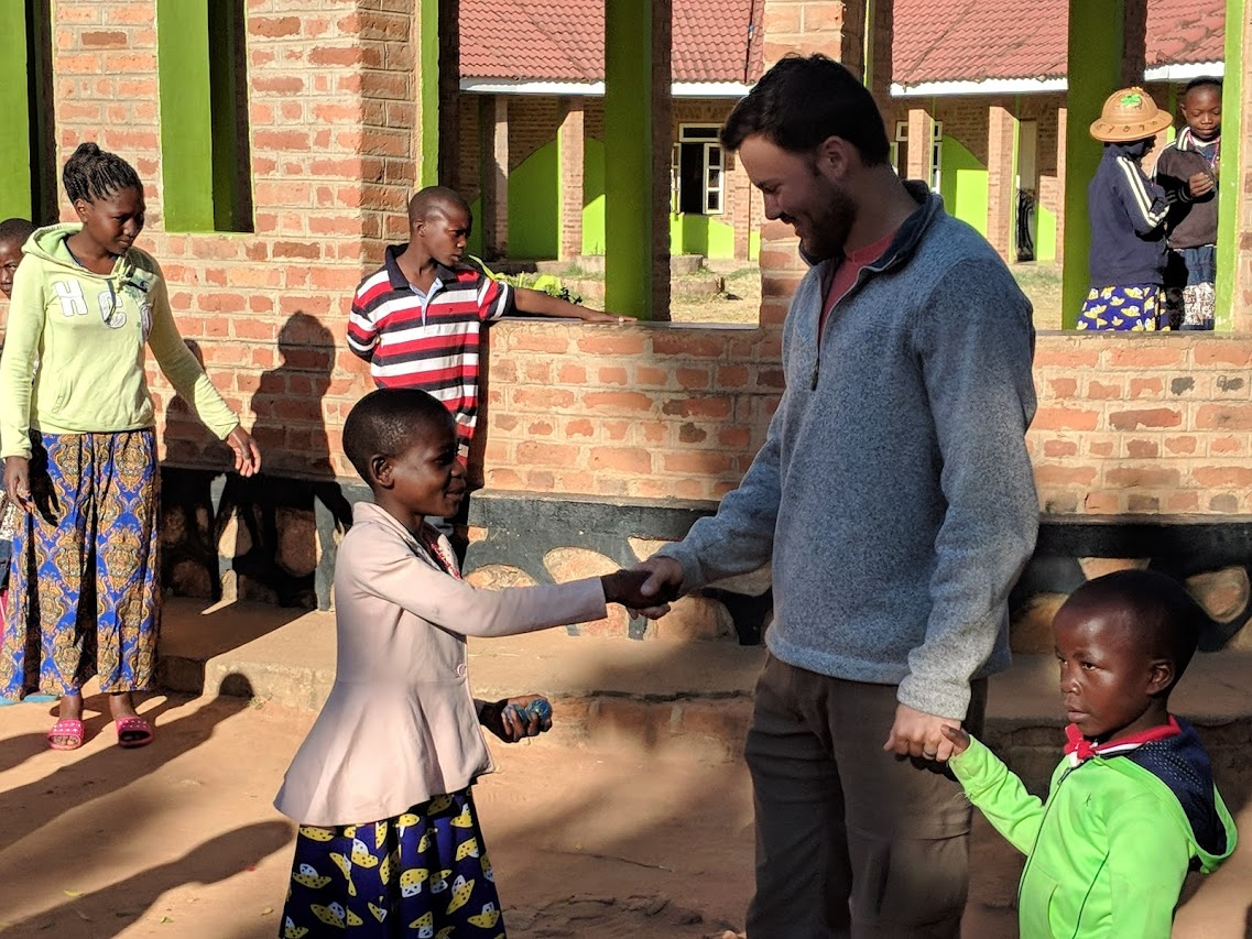 Sam Quinley with kids in Tanzania at Daily Bread Life Children's Home